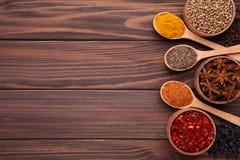Kryddor blandar på träskedar på en brun träbakgrund Top beskådar royaltyfria foton