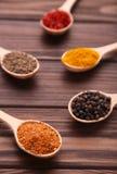 Kryddor blandar på träskedar på en brun träbakgrund Top beskådar fotografering för bildbyråer