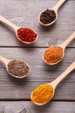Kryddor blandar på träskedar på en grå träbakgrund Top beskådar arkivbild