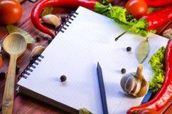 Kryddor, grönsaker och en anteckningsbok arkivfoto