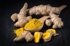 Kryddor; gurkmeja att rota, att klippa, grated på mörk bakgrund arkivfoton