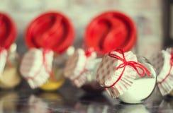 Kryddor i glass krus med härliga räkningar som binds med den röda tråden på den mörka tabellen Fotografering för Bildbyråer
