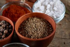 Kryddor i keramiska och glass bunkar på överkanten av trätrumman, närbild, selektiv fokus Fotografering för Bildbyråer