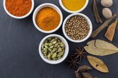 Kryddor i små vita bunkar på svart kritiserar bakgrund - indiskt foto för bästa sikt för krydda arkivbilder