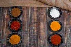Kryddor i svarta keramiska plattor på träbakgrund Royaltyfri Fotografi