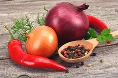 Kryddor, lök, vitlök och chilipeppar på den gamla wood tabellen Arkivbild