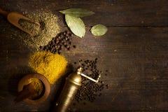 Kryddor och örtar på trä bordlägger royaltyfri foto