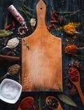 Kryddor och örter med skärbrädan på mörk bakgrund, bästa sikt, kopieringsutrymme royaltyfria bilder