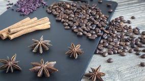 Kryddor och mat på träbakgrund Kanelbruna pinnar, stjärnaanis och kaffebönor Ingredienser för husmanskost royaltyfri foto