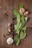 Kryddor och vitlök på en trätabell Arkivbilder