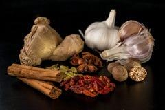 Kryddor på en svart tabell: kanel anis, caien peppar, muskotnöt, royaltyfri fotografi