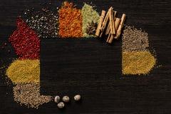 Kryddor på en trätabell för mörk brunt arkivbilder