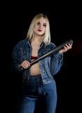 Kryminalna młoda kobieta z kijem bejsbolowym, młodym chuliganem w cajgach i drelichową kurtką, Obraz Stock