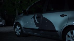 Kryminalny cień z nożem w ręce odbija na parkującej samochód powierzchni, porwanie samochodu zdjęcie wideo