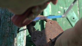 Kryminalny ochrony ochrony pojęcie złodziej łama w dom, piłuje starą metalu żelaza kłódkę z styl życia a zbiory wideo