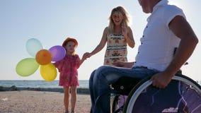 Krymplingen i rullstol med familjen, moder går för hand med dottern bredvid havet, uppfostrar med barnet på öppen luft, mamma lager videofilmer