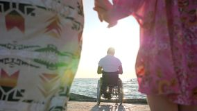 Krymplingen på rullstolen med familj-, moder- och dotteruppehällehänder på bakgrund avlar sammanträde i rullstolar nära bevattnar lager videofilmer