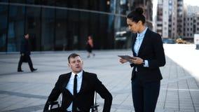 Krymplingframstickandeentreprenören i rullstol ger indikeringar till hans affärskvinnaemploye med IPad stock video
