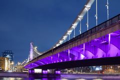 Krymsky Bridge or Crimean bridge in Moscow, Russia night view with purple illumination. Suspension steel bridge over the Moscow River evening time cityscape stock image