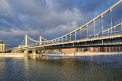 Krymsky Bridge in a Winter Thaw. MOSCOW, RUSSIA - Angle view on the sun lighted Krymsky Crimean Bridge from Pushkinskaya Embankment of Moskva Moscow River area royalty free stock photography