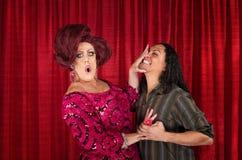 Krypa ihop transvestit och kyssande man Arkivfoto