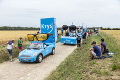 Krys Caravan on a Cobblestone Road- Tour de France 2015 Royalty Free Stock Images