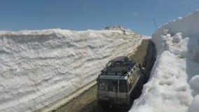kryssare Prado och Mitsubishi Pajero iO som för Av-väg bilToyota land kör på bergvägen i snötunnelen som omges av snödrivor stock video