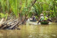 Kryssning för Mekong River deltadjungel med oidentifierad craftman och arkivfoto