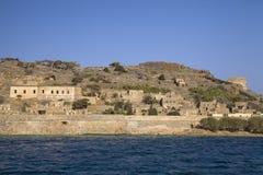 Kryssning till ön av Spinalonga Litet fartyg på den blåa lagun Spinalonga fästning på ön av Kreta, Grekland royaltyfri bild