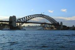 Kryssning under Sydney Harbor Bridge på solnedgången Royaltyfri Bild