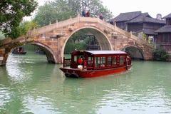 Kryssningfartyg och antik bro i den forntida vattenstaden Wuzhen (Unesco), Kina Arkivbild