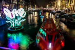Kryssningfartyg rusar i nattkanaler Ljusa installationer på nattkanaler av Amsterdam inom ljus festival Royaltyfri Fotografi