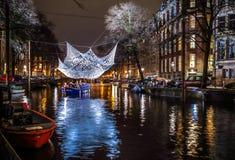Kryssningfartyg rusar i nattkanaler Ljusa installationer på nattkanaler av Amsterdam inom ljus festival Fotografering för Bildbyråer