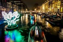 Kryssningfartyg rusar i nattkanaler Ljusa installationer på nattkanaler av Amsterdam inom ljus festival Arkivfoto