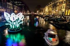 Kryssningfartyg rusar i nattkanaler Ljusa installationer på nattkanaler av Amsterdam inom ljus festival Royaltyfria Bilder