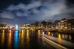 Kryssningfartyg rusar i nattkanaler Ljusa installationer på nattkanaler av Amsterdam inom ljus festival Royaltyfria Foton