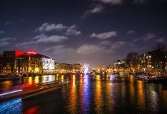 Kryssningfartyg rusar i nattkanaler Ljusa installationer på nattkanaler av Amsterdam inom ljus festival Arkivbild