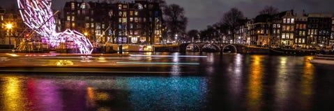 Kryssningfartyg rusar i nattkanaler Ljusa installationer på nattkanaler av Amsterdam inom ljus festival Royaltyfri Bild