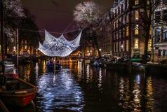 Kryssningfartyg rusar i nattkanaler Ljusa installationer på nattkanaler av Amsterdam inom ljus festival Arkivfoton