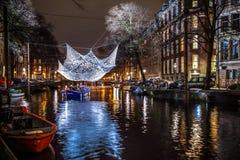 Kryssningfartyg rusar i nattkanaler Ljusa installationer på nattkanaler av Amsterdam inom ljus festival Royaltyfri Foto
