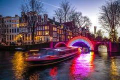 Kryssningfartyg rusar i nattkanaler Ljusa installationer på nattkanaler av Amsterdam inom ljus festival Arkivbilder