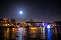 Kryssningfartyg rusar i nattkanaler Ljusa installationer på nattkanaler av Amsterdam inom ljus festival på fullmånen Royaltyfria Foton