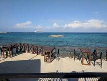 Kryssningskepp som ses från det tomma strandstångkafét arkivfoton
