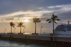 Kryssningskepp vid en pir med palmträd på solnedgången, i Key West, Fl royaltyfria foton