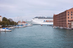 Kryssningskeppet korsar den Giudecca kanalen royaltyfri foto