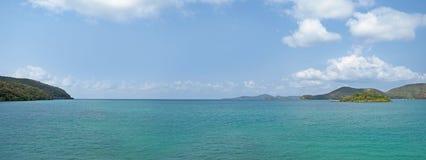 Kryształu zielony ocean z górami i niebieskim niebem z niektóre chmurnieje obraz royalty free