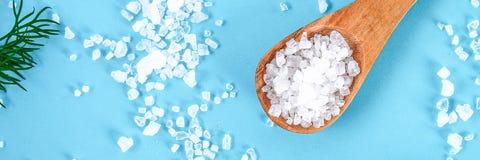 Kryształy wielka morze sól w drewnianym koperze na błękitnym stole i łyżce fotografia royalty free