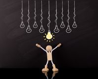 Krytyczny Myślący umiejętności pojęcie, Drewniane kij postaci ręki w górę, Duży Żółty żarówki nakreślenie na chalkboard, zdjęcie stock