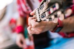 Krzepki męski gitarzysta demonstruje łatwego gitara akord obraz stock