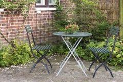 Krzesła i stół w ogródzie idylliczny wiejski chałupa dom zdjęcie royalty free